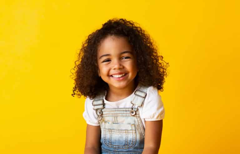 Happy african-american child girl smiling to camera over yellow background